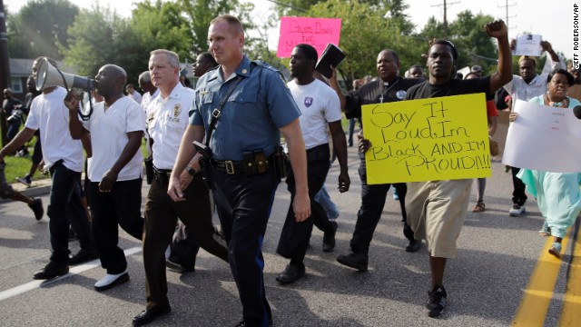 Thousands of demonstrators peacefully march down a street in Ferguson, Missouri, with members of the St. Louis County Police and Missouri Highway Patrol on  Thursday, August 14.