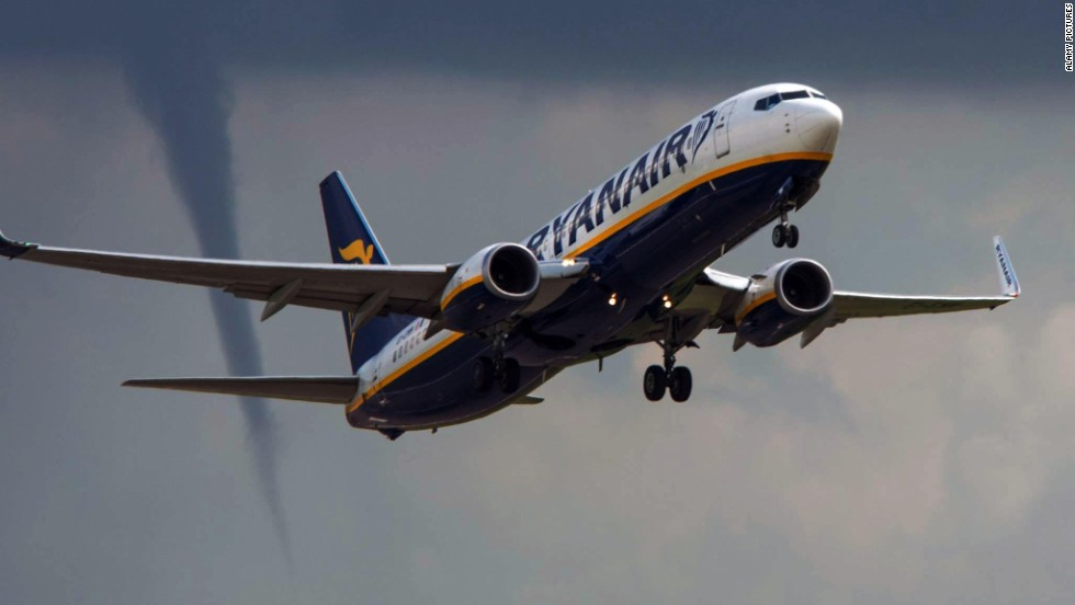 A Ryanair commercial jet takes off from East Midlands Airport in Derby, England, as a tornado funnel forms nearby on Thursday, August 14.