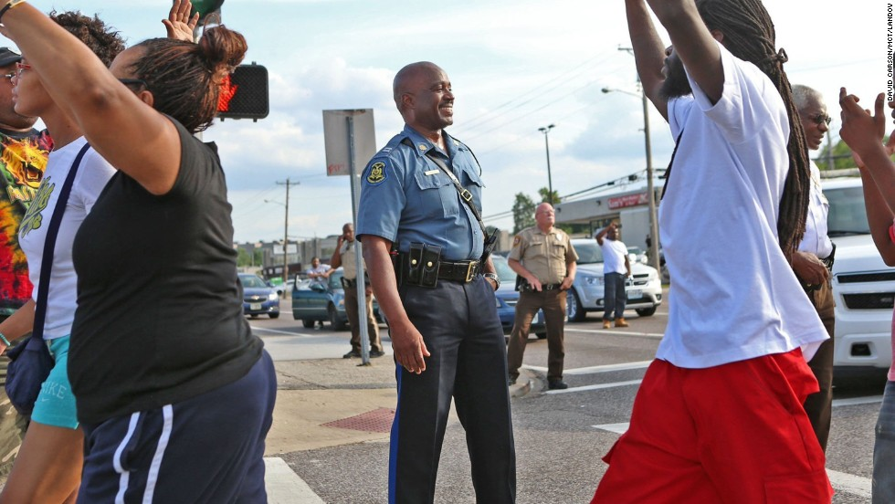 State Highway Patrol Capt. Ron Johnson smiles at demonstrators on August 14, 2014. Johnson was appointed to lead security as state troopers took over after days of clashes between protesters and local police.