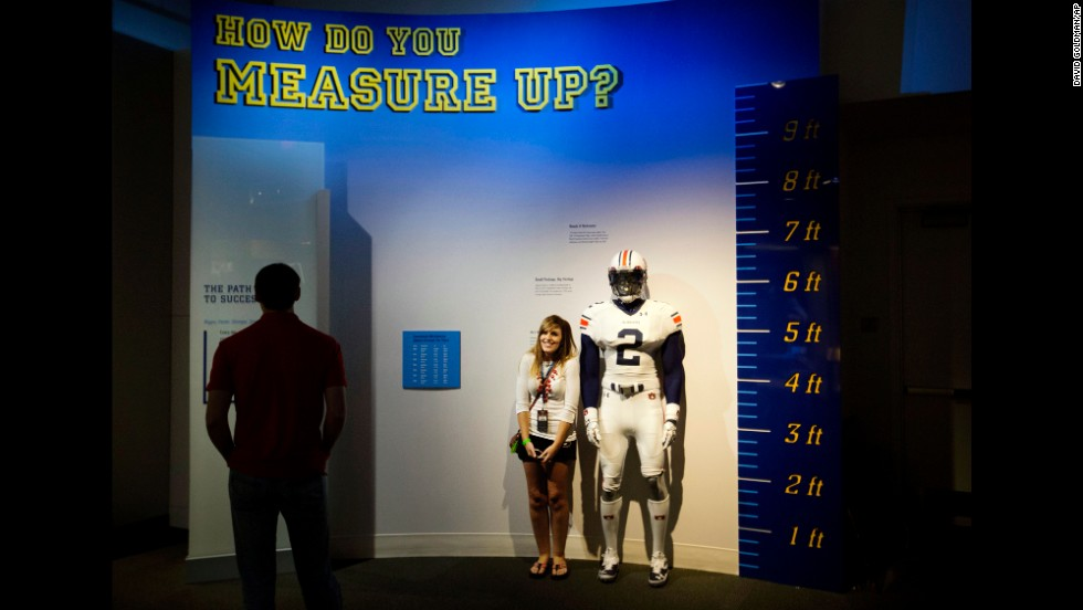 Joanna Jinright measures herself next to a life-size mannequin of a football player dressed like Auburn's Cam Newton.