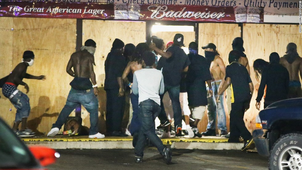 People loot the Ferguson Market and Liquor store on August 16, 2014. Several businesses were looted as police held their positions nearby.