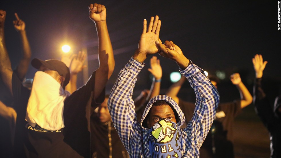 "Demonstrators protest with their hands up on August 15, 2014. The ""hands up"" gesture has become a symbol in protests as Brown, according to eyewitnesses, was trying to surrender when he was shot multiple times."
