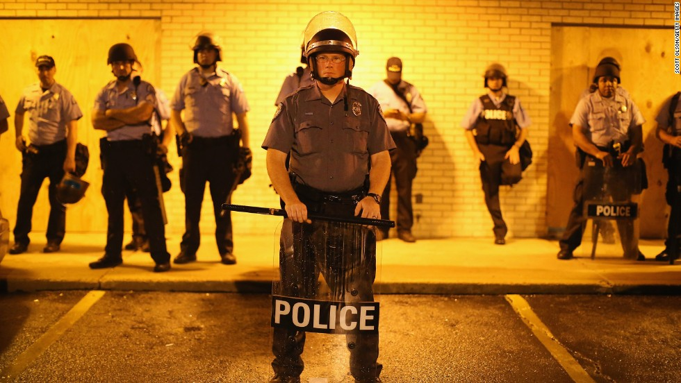 Police stand guard before the midnight curfew on Saturday, August 16, 2014.