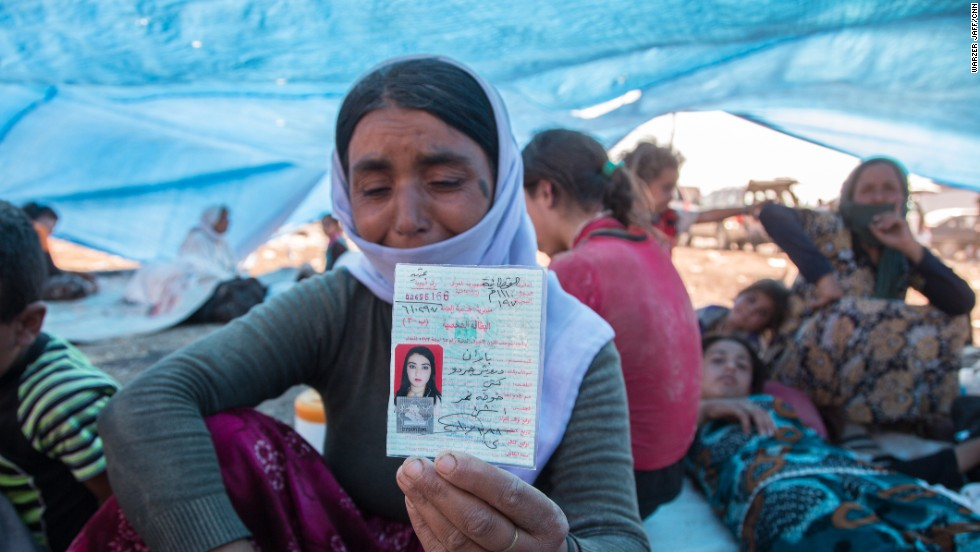 A mother shows the identity card that belonged to her 20-year-old daughter Baran, who was killed by shrapnel while pulling a child to safety.