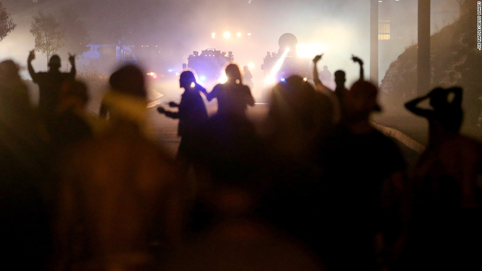 Protesters react as police fire tear gas at them August 17, 2014.