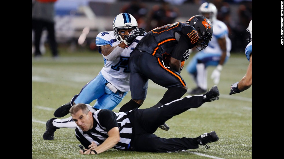 Adam Paradowski, a referee of the Canadian Football League, gets knocked over Sunday, August 17, during a game in Toronto between the Toronto Argonauts and the BC Lions.