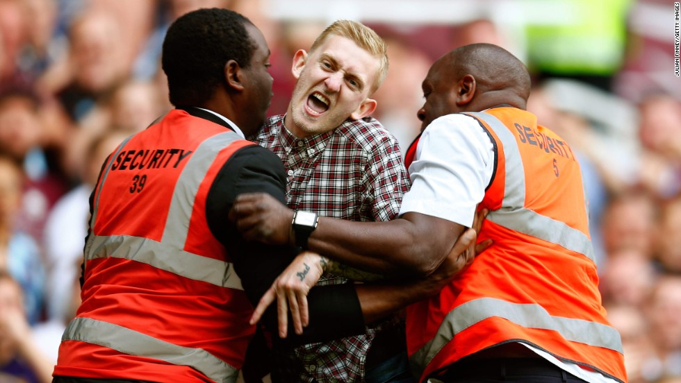 Stewards restrain a man who ran onto the field Saturday, August 16, during the Premier League soccer match between Tottenham and West Ham in London.