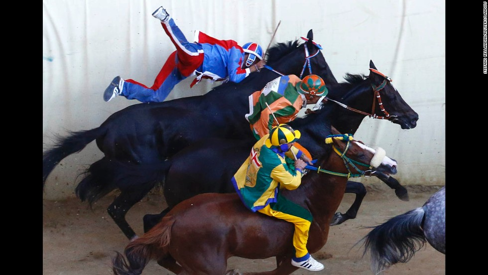 Jockey Sebastiano Murtas, left, crashes during the Palio di Siena horse race Saturday, August 16, in Siena, Italy. Twice a year, 10 riders — each representing one of Siena's city wards — compete in the bareback race around Siena's shell-shaped central square.