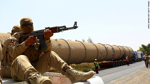 A section of an oil refinery is guarded as it is brought on a lorry to the Kawergosk Refinery, some 20 kilometres east of Arbil, the capital of the autonomous Kurdish region of northern Iraq, on July 14, 2014. The International Energy Agency (IEA) said on July 11, that an offensive by jihadists in northern Iraq had cut output by 260,000 barrels a day in June to 3.17 million, after fighting forced the closure of the country's biggest refinery and slashed production from the giant Kirkuk field