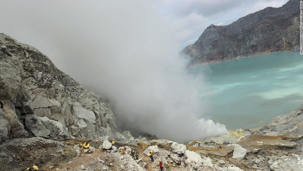 "The deceivingly inviting turquoise lake of Kawah Ijen in Indonesia is composed of sulfuric acid. The volcano is famous for ""blue fire"" caused by sulfur gas burning as liquid sulfur cools into yellow blocks that miners cart away. It's best to watch your step on a volcano, even more so with a skin-melting lake."