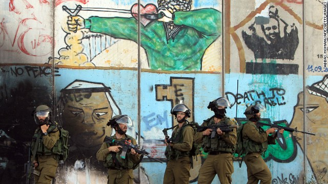 Israeli soldiers stand in front of the graffiti covered controversial separation-barrier during clashes with Palestinian stone throwers who rallied to show their support for the Gaza Strip following a month of fighting between the Israeli military and Hamas militants, at the Israeli Qalandiya checkpoint between the West Back city of Ramallah and Jerusalem, on August 13, 2014.