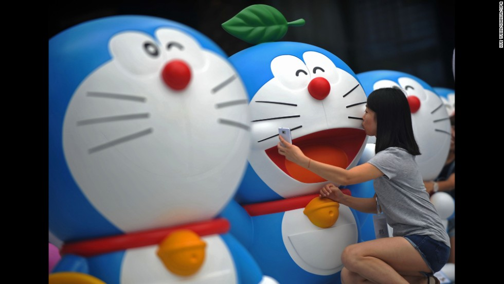A visitor takes a selfie with a Doraemon figure during a Doraemon exhibition in Chengdu, China, on Saturday, August 16. Doraemon, a robotic cat from the 22nd century, has been a popular anime character since 1969.