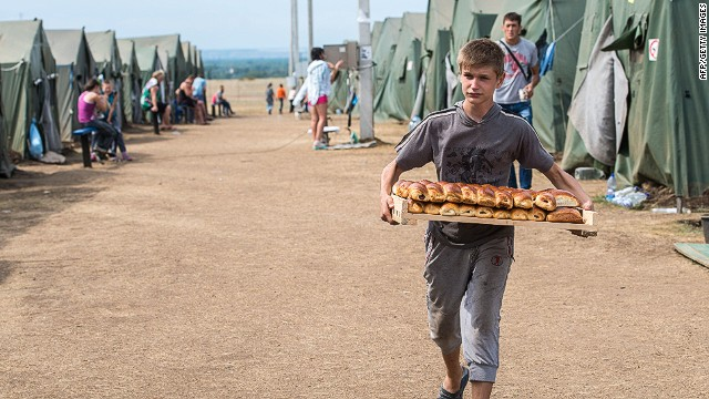 A boy carries pastries in refugee camp near the Russian city of Donets'k, Rostov region, about 15 kilometers from the Russian-Ukrainian border. Some 285,000 people have already fled their homes due to the conflict in east Ukraine, it is estimated, with many leaving for other parts of the country, but close to 168,000 seeking sanctuary in Russia. AFP PHOTO / DMITRY SEREBRYAKOVDMITRY SEREBRYAKOV/AFP/Getty Images