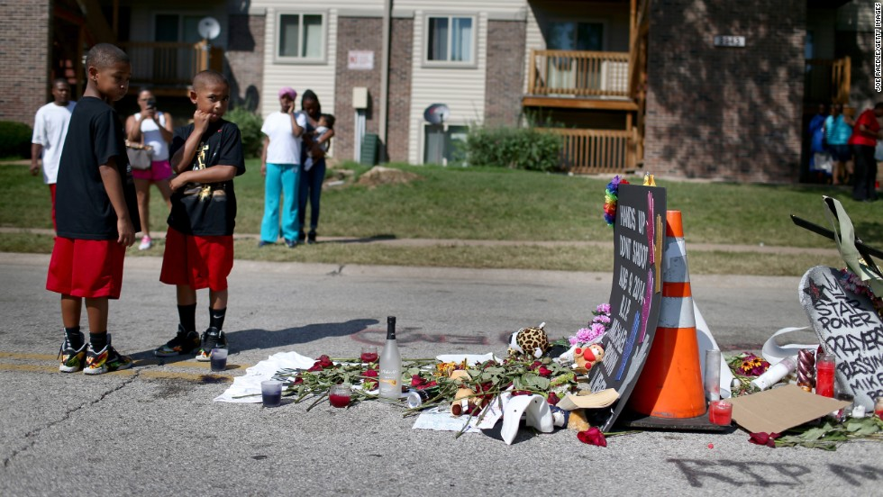 People on August 19 stand near a memorial where Brown was shot and killed, 2014.