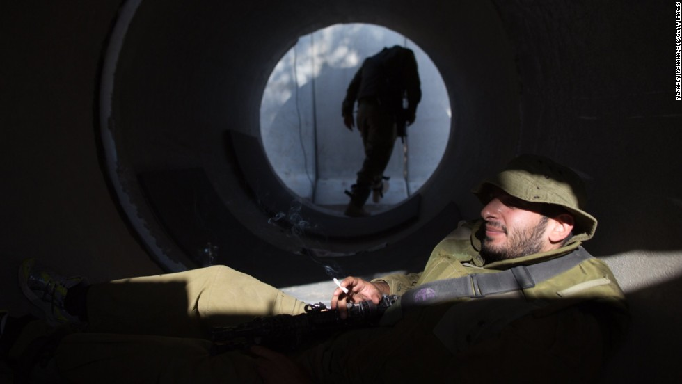 An Israeli soldier smokes a cigarette in a large concrete pipe used as shelter at an army deployment point near the Israeli-Gaza border on Wednesday, August 20.