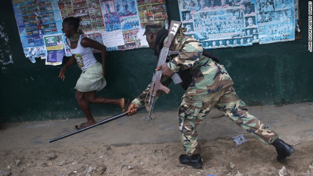 MONROVIA, LIBERIA - AUGUST 20:  A Liberian Army soldier, part of the Ebola Task Force, beats a local resident while enforcing a quarantine on the West Point slum on August 20, 2014 in Monrovia, Liberia. The government ordered the quarantine of West Point, a congested seaside slum of 75,000, on Wednesday, in an effort to stop the spread of the virus in the capital city. Liberian soldiers were also sent in to the seaside favela to extract West Point Commissioner Miata Flowers and her family members after residents blamed the government for setting up a holding center for suspected Ebola patients to be set up in their community. A mob overran and closed the facility on August 16. The military also began enforcing a quarrantine on West Point, a congested slum of 75,000, fearing a spread of the epidemic. The Ebola virus has killed more than 1,200 people in four African nations, more in Liberia than any other country.  (Photo by John Moore/Getty Images)