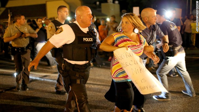 Police officers escort a protester supporting Officer Darren Wilson to a police vehicle away from agitated protesters in support of Michael Brown in Ferguson, Missouri, on Wednesday, August 20.