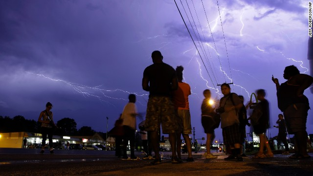 Lightning streaks across the night sky over protesters on August 20. The streets of Ferguson emptied out by early Thursday for the first time since Michael Brown was killed.