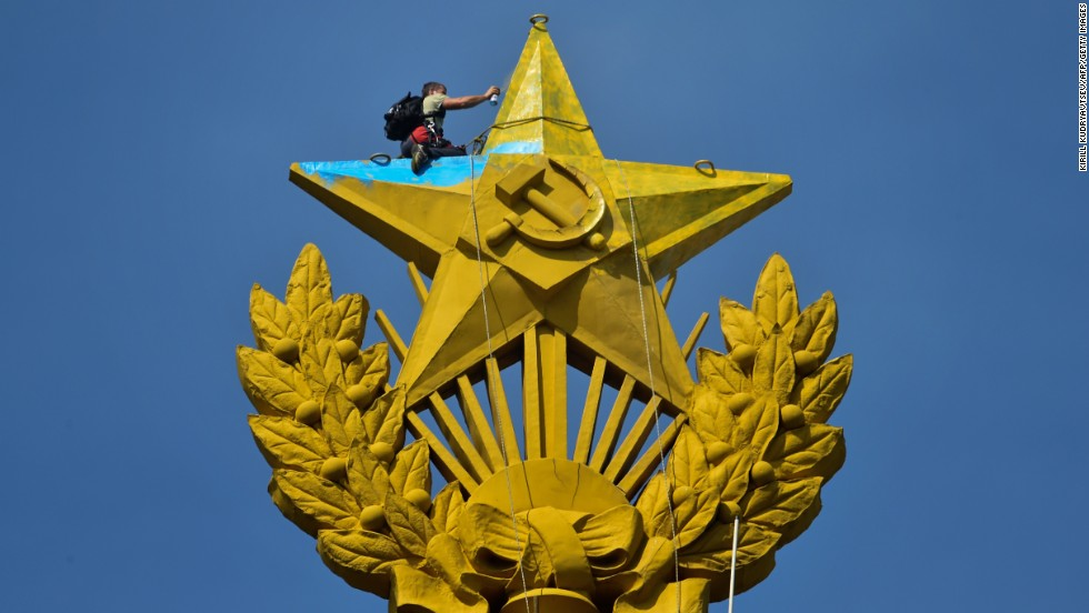 A worker repaints the top of a Stalin-era skyscraper in Moscow on Wednesday, August 20. The giant star had been painted in yellow and blue, Ukraine's national colors, by unknown people. A Ukrainian flag was also hung from the star.