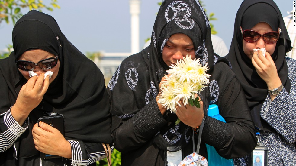 People cried as they waited outside Bunga Raya Complex at Kuala Lumpur International Airport before victims' bodies were flown back from Amsterdam.