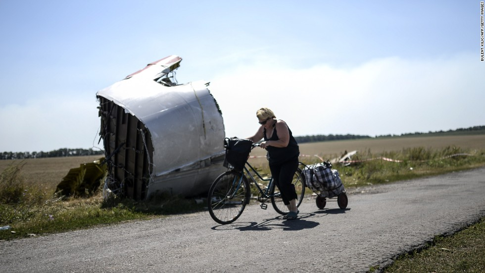 A woman walks with her bicycle near the crash site on August 2, 2014.