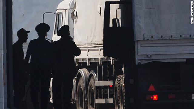 A driver, left, and Russian custom service officers stand near trucks of the Russian aid convoy which are searched at a Russian inspection zone inside a border control point with Ukraine in the Russian town of Donetsk, Rostov-on-Don region, Russia, Friday, Aug. 22, 2014. The first trucks of the Russian aid convoy crossed the Ukrainian inspection zone Friday morning. (AP Photo/A driver, left, and Russian custom service officers stand near trucks of the Russian aid convoy which are searched at a Russian inspection zone inside a border control point with Ukraine in the Russian town of Donetsk, Rostov-on-Don region, Russia, Friday, Aug. 22, 2014. The first trucks of the Russian aid convoy crossed the Ukrainian inspection zone Friday morning. (AP Photo/Pavel Golovkin))