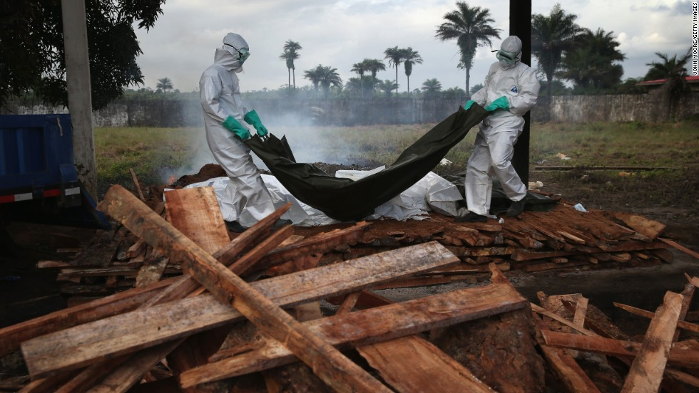 A burial team from the Liberian Ministry of Health unloads bodies of Ebola victims onto a funeral pyre at a crematorium in Marshall, Liberia, on August 22, 2014.