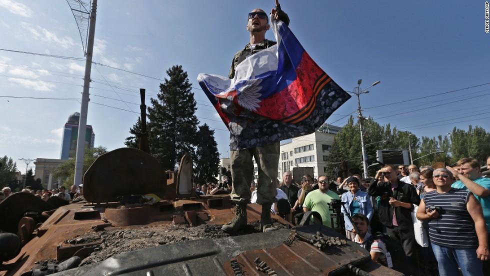 A pro-Russian rebel delivers a speech atop a damaged Ukrainian armored personnel carrier in Donetsk on August 24.