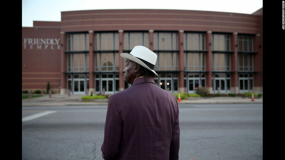 James Wright waits for the Friendly Temple Missionary Baptist Church to open for the funeral service.