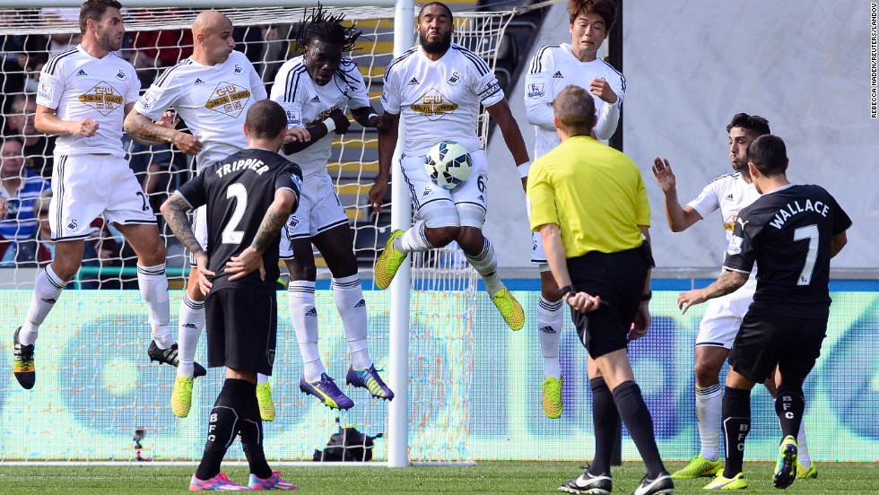 Swansea City's Ashley Williams, center, stops a free-kick taken by Burnley's Ross Wallace during a English Premier League soccer match at Liberty Stadium in Swansea, Wales, on Saturday, August 23. Swansea City won 1-0.