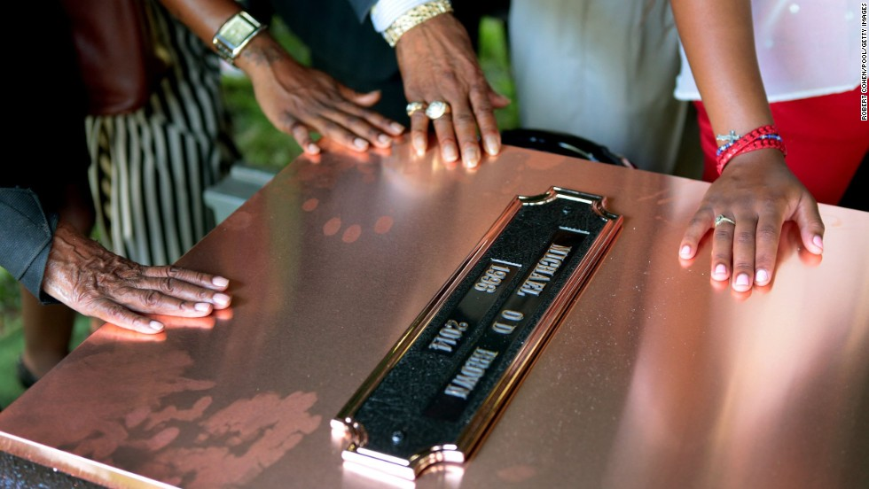 Family members touch the copper top of the vault containing Brown's casket.