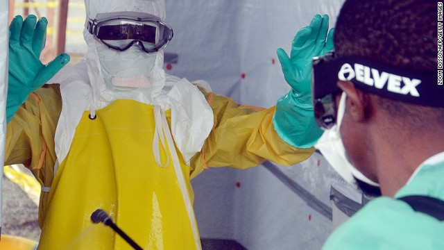 A picture taken on August 21, 2014 shows a nurse disinfecting a doctor's protective gear at the French NGO Medecins Sans Frontieres (MSF - Doctors Without Borders) ELWA hospital in Monrovia, where patients suffering from Ebola are taken care of.