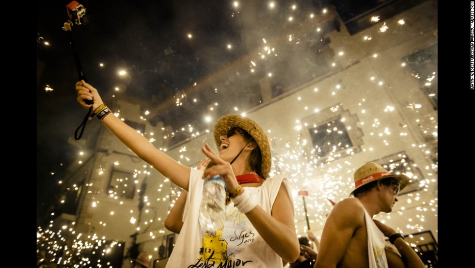"A girl takes a selfie in front of the fire-runners setting off their fireworks during the ""Festa Major de Sitges"" on Saturday, August 23, in Spain."