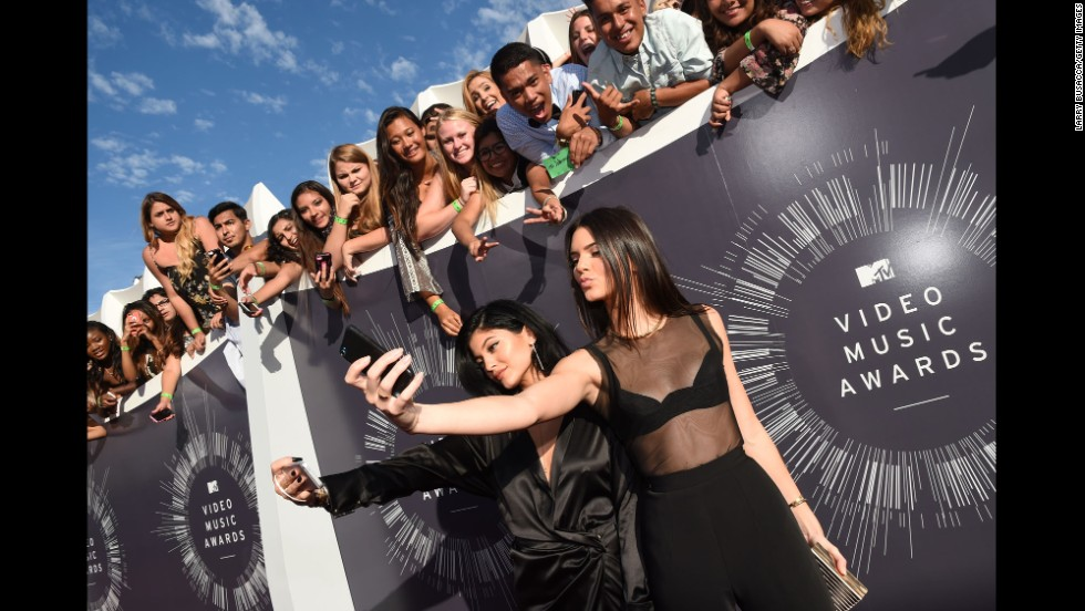 Models and TV personalities Kylie Jenner, left, and Kendall Jenner take selfies with fans on the red carpet at the 2014 MTV Video Music Awards on Sunday, August 24.