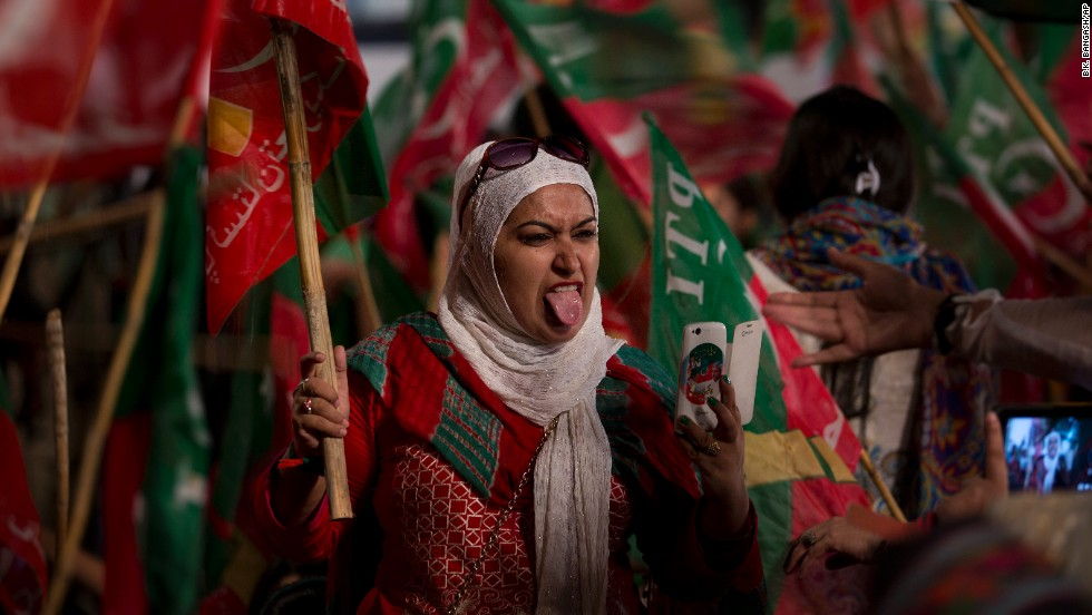 A supporter of Pakistan's cricket celebrity-turned-politician Imran Khan sticks out her tongue while taking a selfie during a rally in Islamabad, Pakistan, on Saturday, August 23. Thousands of supporters of Khan and cleric Tahir-ul-Qadri's are besieging parliament to pressure Prime Minister Nawaz Sharif to resign over alleged election fraud.