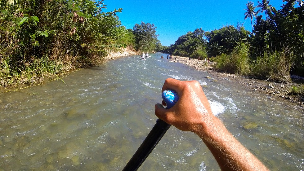 There's more than surfing. A standup paddleboard trip to nearby Wanukaku river winds through local villages ...