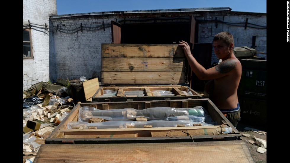 A man opens a box filled with rocket-propelled grenades left by the Ukrainian army in Starobesheve.