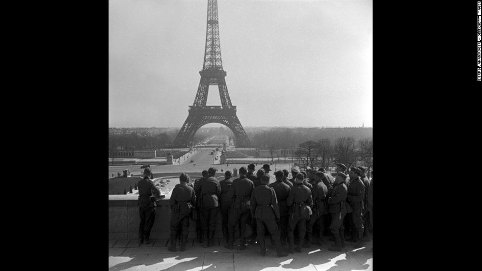 German soldiers on the Esplanade du Trocadero view the Eiffel Tower. In June 1940, German troops marched into Paris, forcing France to capitulate and establish the pro-Axis Vichy French government.