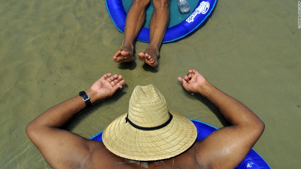 Ron Mcgee, bottom, and Shawn Williams sunbathe in a shallow tidal pool in Tybee Island, Georgia, on Saturday, August 23.