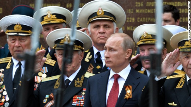 Caption:Russia's President Vladimir Putin (C) and World War II veterans watch a parade of honour guard during his visit to the Crimean port of Sevastopol on May 9, 2014. Putin's visit to Crimea, which was annexed by Moscow in March, is a 'flagrant violation' of Ukraine's sovereignty, authorities in Kiev said today. AFP PHOTO/ YURI KADOBNOV (Photo credit should read YURI KADOBNOV/AFP/Getty Images)