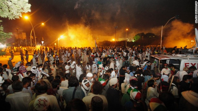 Pakistani protesters run during clashes near prime minister's home in Islamabad, Pakistan, Saturday, Aug. 30, 3014. Pakistani police fired tear gas at thousands of protesters as they tried to march toward the prime minister's home in the capital on Saturday, blanketing the route with clouds of white smoke and scattering demonstrators. (AP Photo/Anjum Naveed