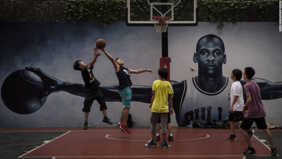 Students in Beijing play basketball on a court that has a poster of NBA great Michael Jordan on Monday, September 1. Basketball is one of the fastest-growing youth sports in China.