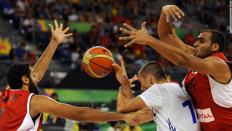 Egyptian forwards Seif Samir, left, and Amr Gendy, right, defend France's Kim Tillie during a FIBA World Cup game Monday, September 1.