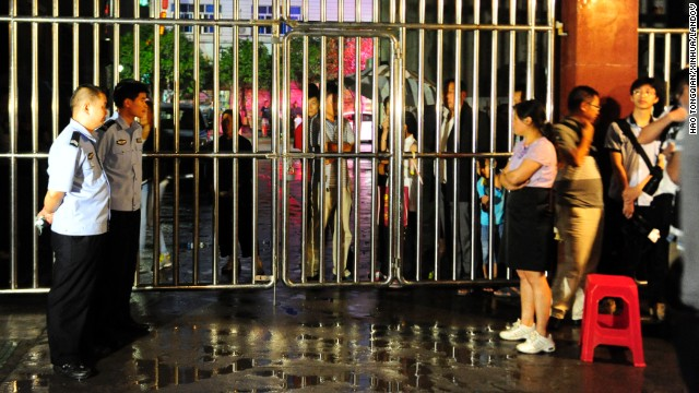 Locals and guards stand at the gate of the Dongfang Primary School after Monday's deadly attack.