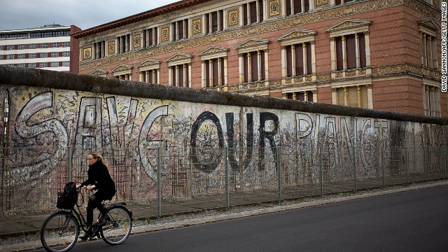 A woman cycles past a part of the Berlin Wall with the Martin-Gropius-Bau gallery in the background .