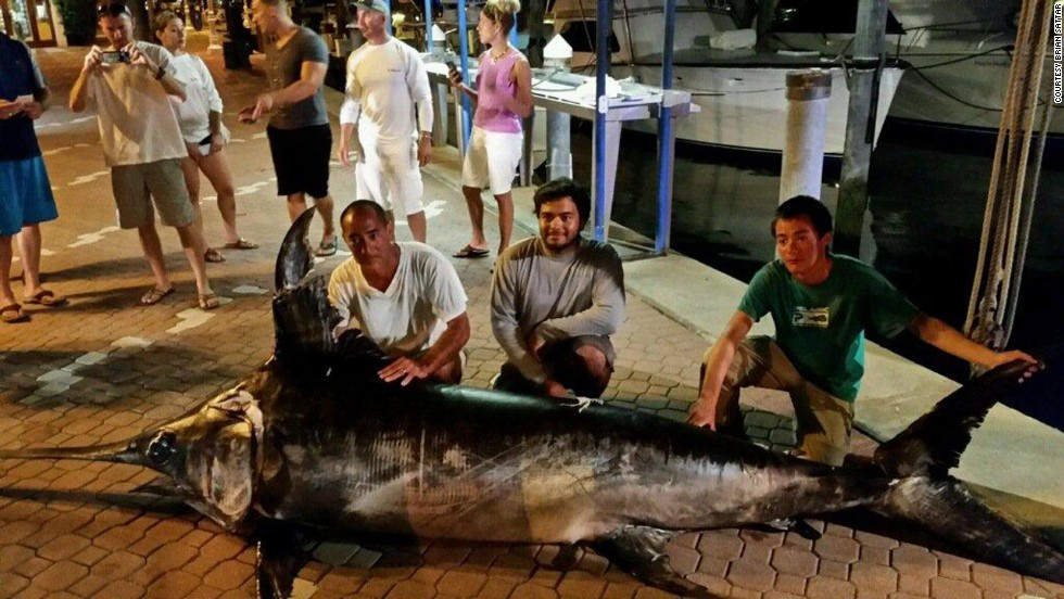 The family, from North Palm Beach, Florida, poses with the swordfish at the marina. Because the fish was caught with an electric reel, it won't be considered for a state record.