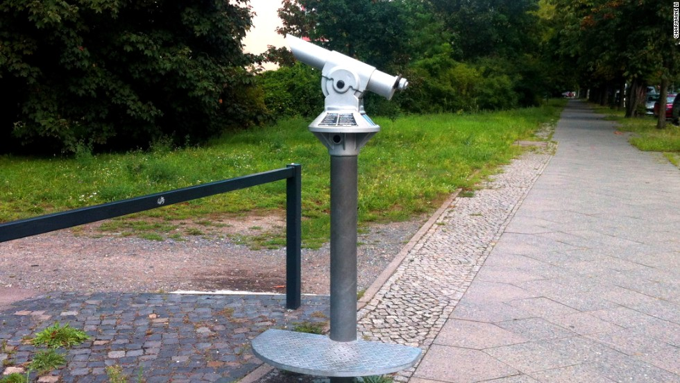 """Ubergang -- Nahe und Distanz"" (Crossing -- Proximity and Distance) by Heike Ponwitz stands at the former Sonnenallee border crossing. Inconspicuous gray telescopes symbolize mass surveillance during the era of the Berlin Wall."