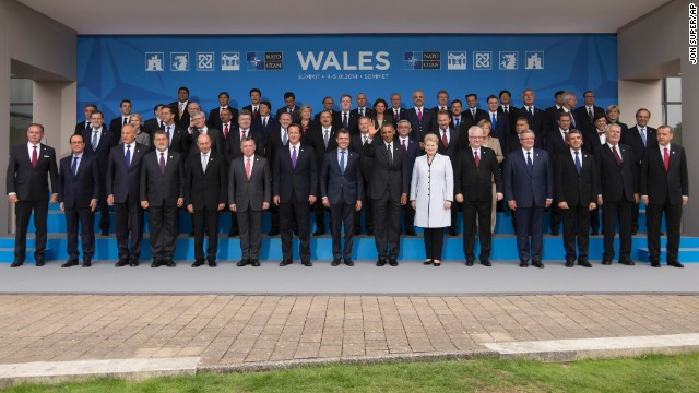 U.S. President Barack Obama, bottom center, waves during a group photo opportunity at a NATO summit on the grounds of the Celtic Manor Resort in Newport, Wales on Thursday, Sept. 4, 2014. World leaders gathered at a golf resort in Wales for a high-stakes NATO summit. While the official agenda will focus on the crisis in Ukraine and the drawdown of the NATO combat mission in Afghanistan, the rise of the Islamic State group in Iraq and Syria will dominate discussions on the sidelines of the summit. (AP Photo/Jon Super)