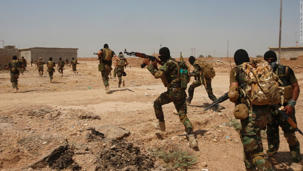 """Shiite militia fighters run during a mission Monday, September 1, in Tikrit, Iraq. They have been <a href=""""http://www.cnn.com/2014/06/13/world/gallery/iraq-under-siege/index.html"""">battling the militant group ISIS,</a> which is seeking to create an Islamic caliphate that stretches from Syria to Iraq."""