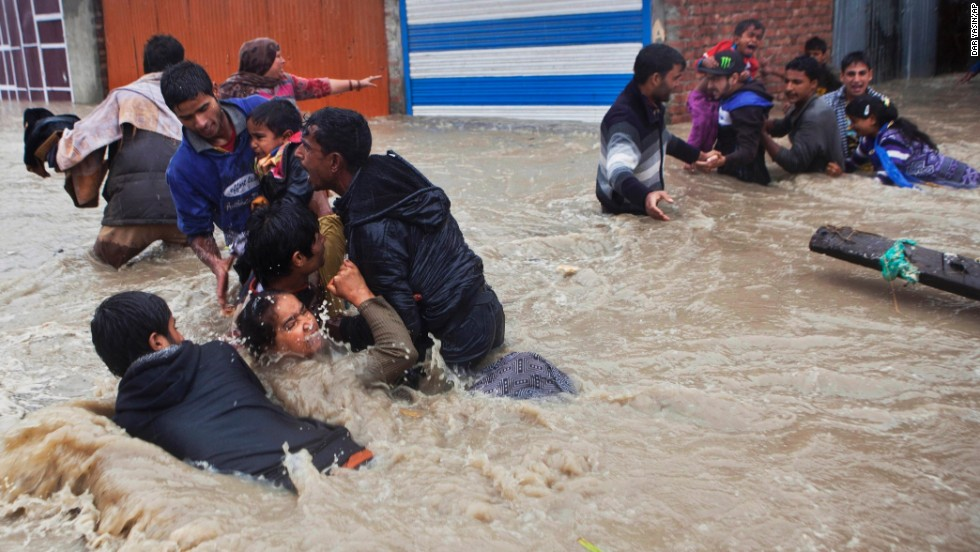 "People struggle to wade through floodwaters Thursday, September 4, in Srinagar, India. Many villages and urban areas in Indian-administered Kashmir <a href=""http://www.cnn.com/2014/09/04/world/asia/india-bus-accident/index.html"">have been flooded</a> after heavy rain made lakes and rivers overflow."